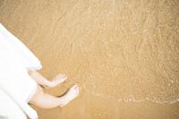 浅瀬の砂浜に佇む女性の足下