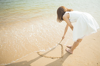 浅瀬の砂派にハートを描く女性