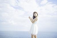 海辺で携帯を持つ女性
