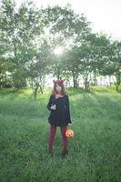 夕暮れの公園に立つハロウィンの仮装をした女性
