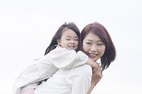 笑顔でおんぶする母と子供