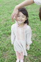 笑顔で芝生に立つ子供と母親の手