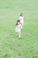 芝生を駆ける子供と母親