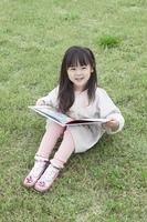 芝生で絵本を読む子供