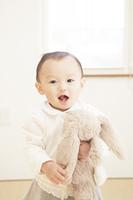 ぬいぐるみを持って笑う赤ちゃん