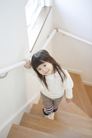 手すりを持って階段を上がる女の子