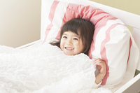 ベッドに笑顔で寝る女の子