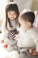 ベッドで積み木で遊ぶ女の子と赤ちゃん