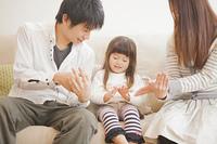 ソファーに座って遊ぶ家族