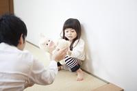 父親とぬいぐるみで遊ぶ女の子
