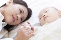 赤ちゃんの手を握る母親