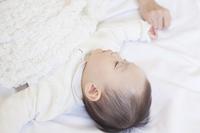 眠る赤ちゃんと手をつなぐ母親