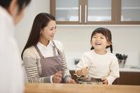 母親と料理をする笑顔の女の子