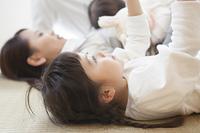 畳で寝転ぶ女の子と母親