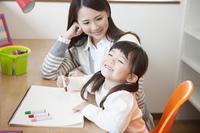 母親と絵を描く女の子