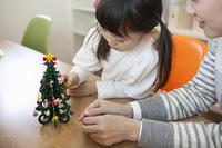 母親とクリスマスツリーを飾り付ける女の子