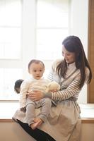 赤ちゃんをひざに上で抱く母親