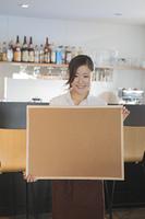 コルクボードを持つ女性カフェ店員