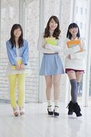 ノートを持って3人並んで歩く女子学生