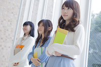 ノートを持って3人で並ぶ女子学生
