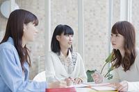 テーブルで一緒に勉強する女子学生