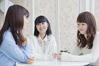 座って3人で会話をする女子学生