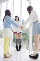 輪になって手をつなぐ3人の女性