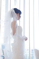 教会に立つウエディングドレス姿の女性