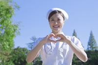手でハートの形を作る看護士