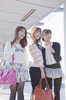 友達と遠くを見つめるバッグを持つ女性