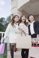 友達とショッピングバッグを持って同じ方向を見つめる笑顔の女性