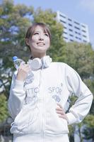 公園でペットボトルを持ってヘッドフォンをする女性