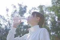 公園で水を飲む女性