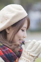 マフラーをしてマグカップを持つ手袋をした女性