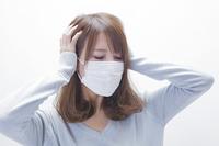 頭をおさえるマスクをした女性