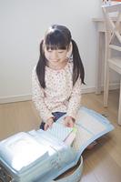 ランドセルに教科書を入れる小学生の女の子