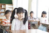 机につく小学生