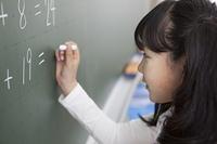 黒板に答えを書く小学生
