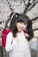 桜をバックに立つ小学生