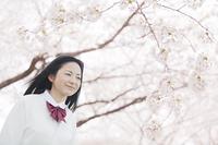 桜をバックに立つ高校生