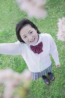 桜の木の下で手をあげる高校生