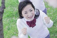 桜の木の下でガッツポーズをする高校生