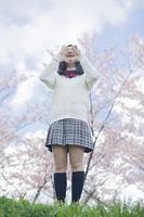 桜をバックに応援をする高校生