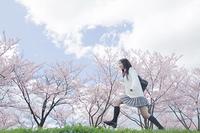 桜をバックにジャンプをする高校生