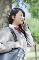 木陰で電話をする高校生