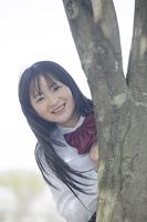 木の幹から顔を出す高校生