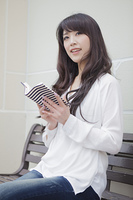 ベンチで本を読む女性