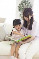 お母さんにソファーで絵本を読んでもらう女の子