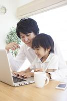 子供と一緒にパソコンを見る男性