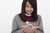 ガラスの地球儀を持つ高校生